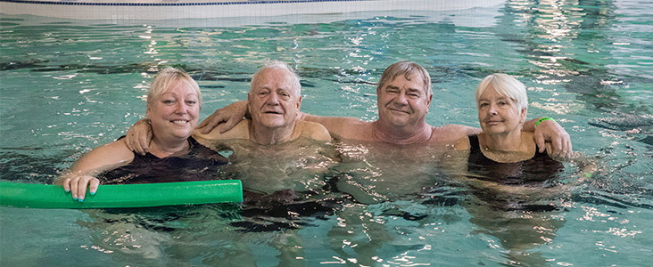 Photo of four seniors swimming in a pool.