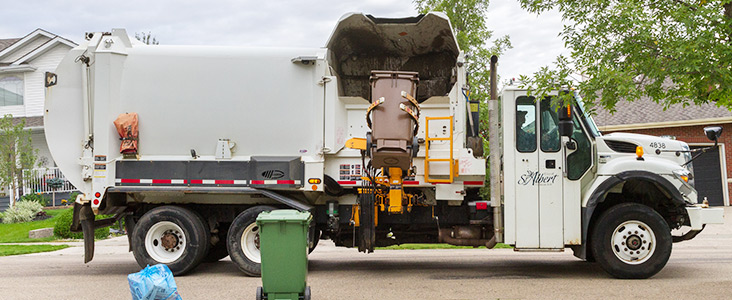 Garbage truck picking up waste cart