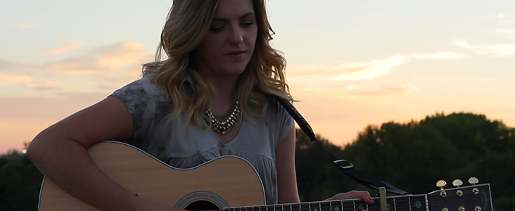 Youth playing the guitar with sunset in the background