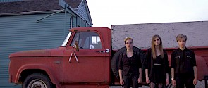 Three youths standing in front of a truck