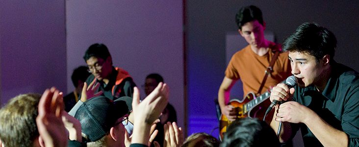 Performers singing and playing guitar in front of crowd