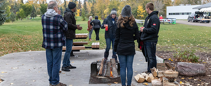 people standing around a fire pit