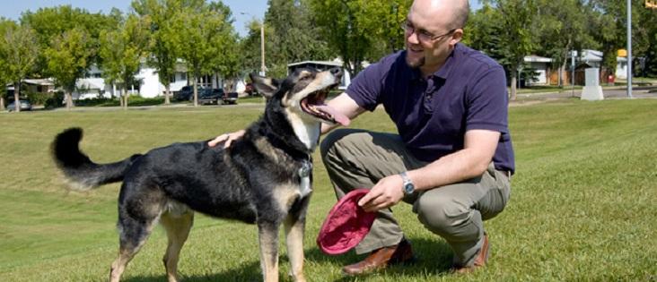 Photo of man crouching beside a dog