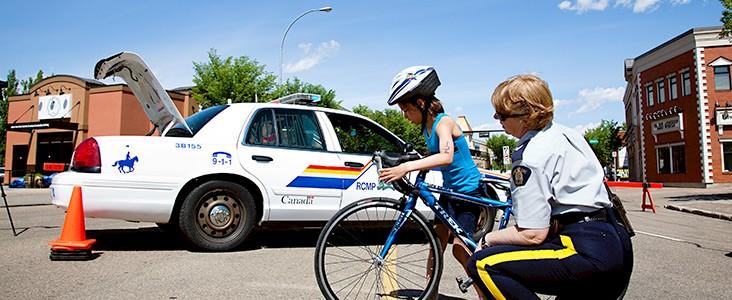 RCMP Officer helping girl on bike