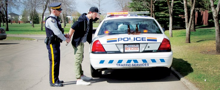 Photo of an RCMP officer putting handcuffs on a youth who is standing beside a police car