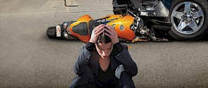 Photo of girl sitting with her head in her hands with a motorcycle accident in the background