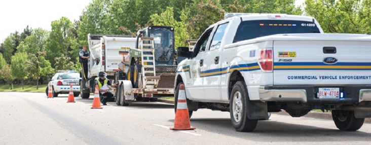Photo of two RCMP vehicles on either side of a dump truck pulling a forklift