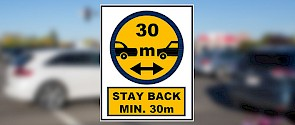 Photo of traffic that is blurry with a sign on top that says Stay back minimum of 30m