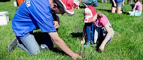 Photo from Spruce Up with people helping to plant trees along the river