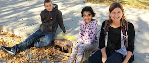 Photo of woman, girl and boy sitting on a side walk