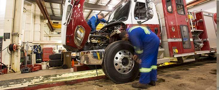 Two Public Works staff working on firetruck