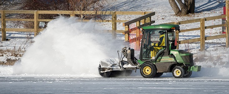 Machine brushing snow off a pond