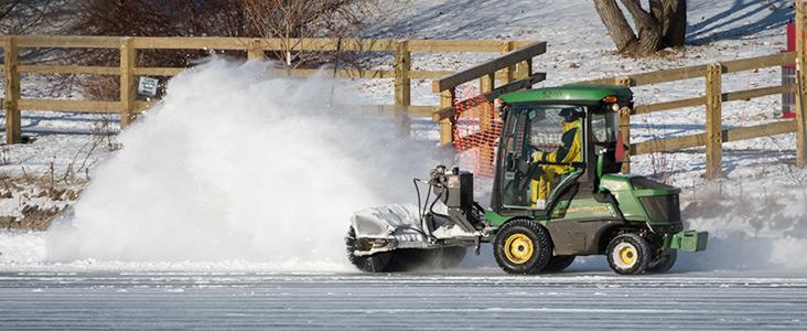 Machine brushing snow off a pond