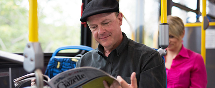 Photo of a man sitting on a bus reading the newspaper