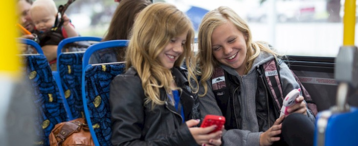 Photo of two girls riding the bus together sharing what is on their phones with each other
