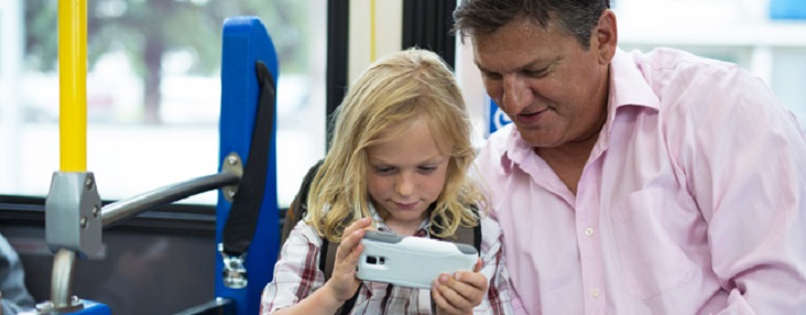 Picture of a man and girl sitting on a bus looking at the screen of a phone