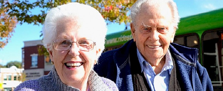Photo of an elderly couple standing in front of a Handibus smiling