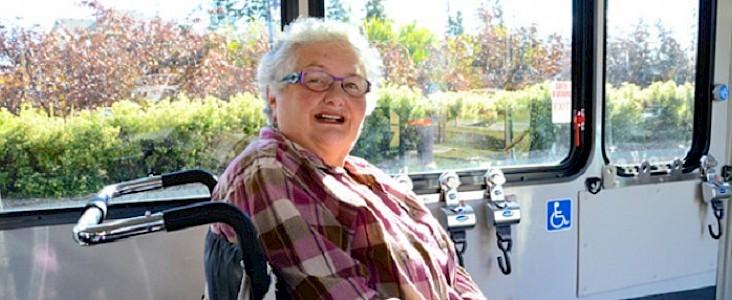 Photo of a senior woman sitting on a Handibus smiling