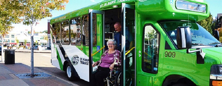 Photo of a driver pushing a woman in a wheelchair out the front door of the bus