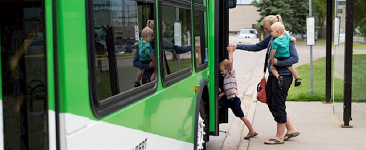 Photo of a woman, who is carrying a toddler and holding the hand of a young boy, is getting on a bus