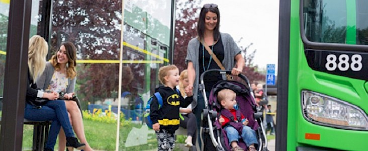 Photo of a woman who pushing a stroller and holding the hand of a young boy about to get on a bus