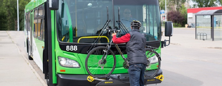 Photo of a person putting their bike in the bike rack on the front of the bus