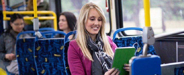 Photo of a sociopath sitting on a bus with their tablet