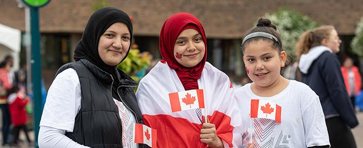 Three women holding Canada flags