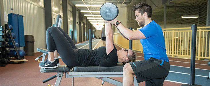 Personal trainer with client spotting free weights