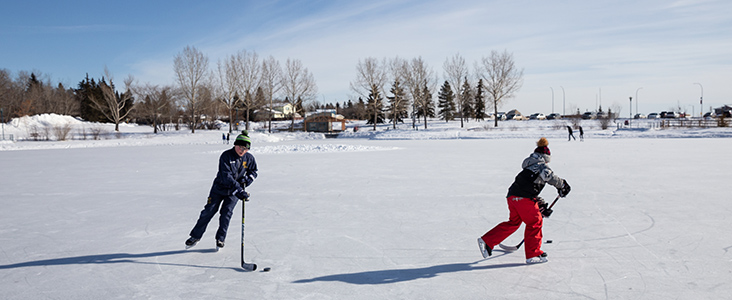 Kids playing hockey on a pond