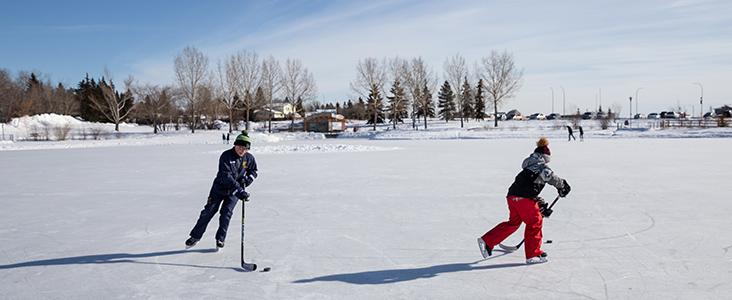Kids playing hockey on a pond