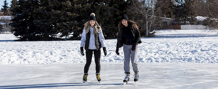 Two skaters on an outdoor rink