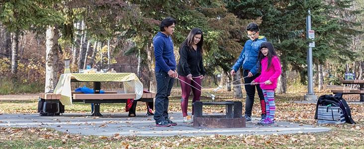 Happy family roasting marshmallows in Lions Park in Saint Albert, Alberta