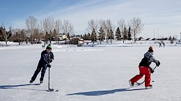 two people playing ice hockey outside