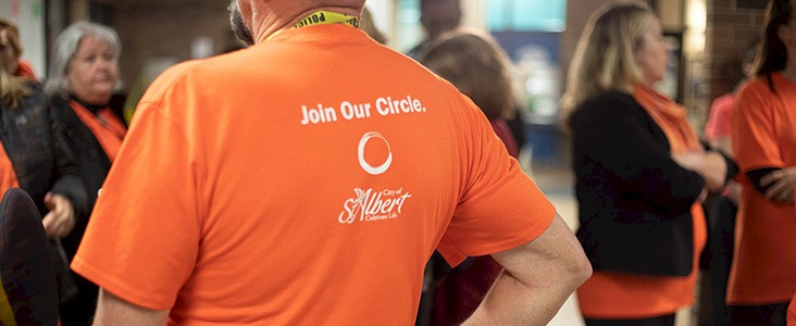 A volunteer wearing an orange City of St. Albert shirt