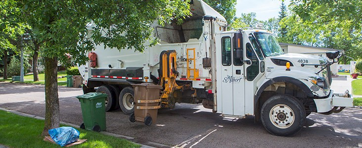 City waste truck picking up brown organics cart