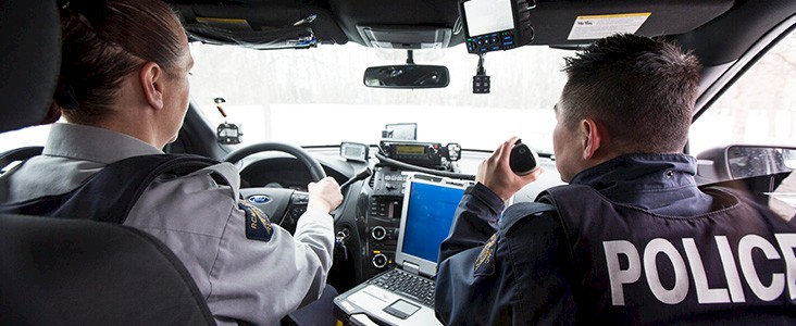 Two RCMP officer in a car responding to an emergency