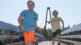 Kids running across the Children's Bridge in Red Willow Park