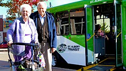 A senior couple stand in front of a Handibus