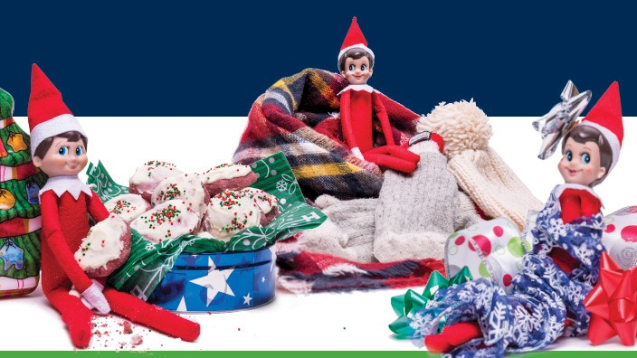 3 elves sitting in holiday items and decorations