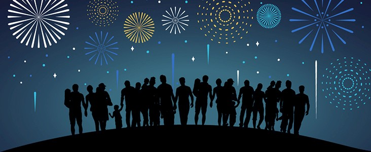 Silhouettes of people enjoying a fireworks display