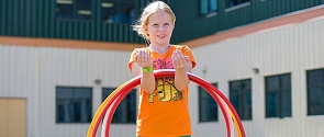 Summer camper at Servus Place in Saint Albert smiles while playing with hula hoops