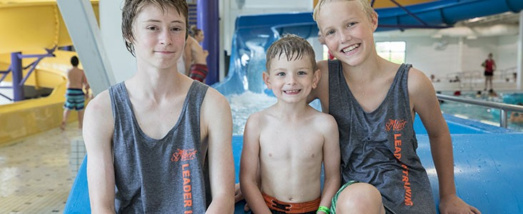 Two leaders in training smile with summer camp participant on waterslide