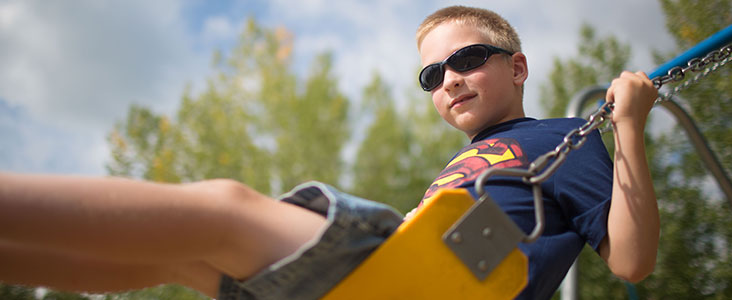 Boy wearing sunglasses smiles at camera while on swing at Lions Park