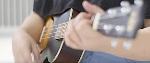 Close up photo of a youth playing guitar