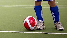 Close up photo of soccer player's feet kicking a soccer ball