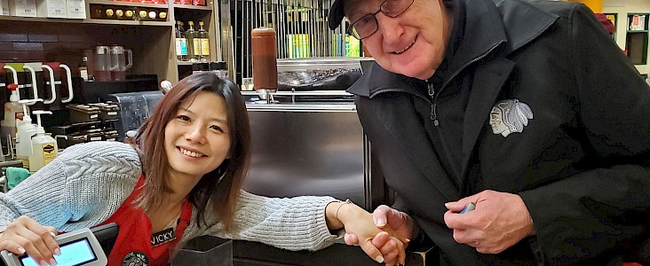 Starbucks employee smiles and holds hands with smiling Servus Place patron