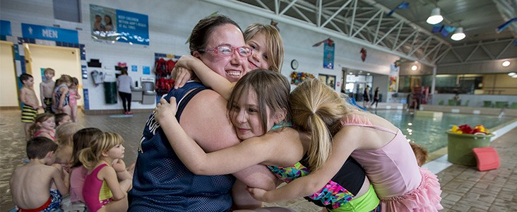 Instructor hugging swimming students