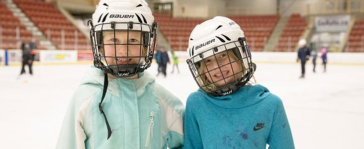 Two girls smile at the camera while skating on an indoor ice rink.