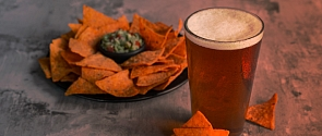A nacho platter and a refreshing pint of beer